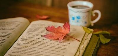 Une feuille d'automne posée sur un livre ouvert et une tasse de café sur une table en bois