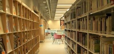 Rayonnages de la bibliothèque avec dans le fond une salle de lecture