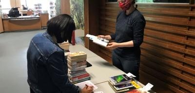 Deux bibliothécaires de part et d'autre d'une table préparent des piles de livres