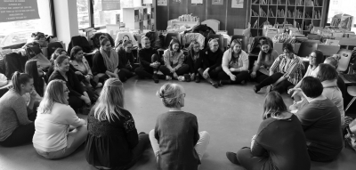 Adultes assis en rond au milieu d'une bibliothèque