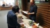 Deux bibliothécaires de part et d'autre d'une table préparant des piles d'ouvrages à emprunter