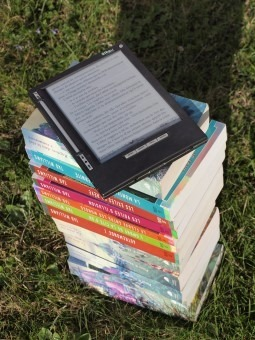 Liseuse électronique posée sur une pile de livres, sur une pelouse